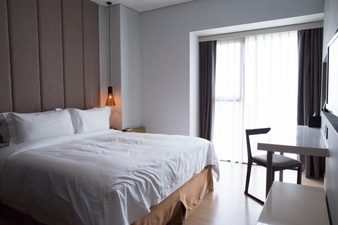 hotel-bedroom-with-double-bed-table-and-tv-set_1262-3034