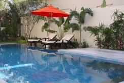 pool area with sunchairs and umbrella 005